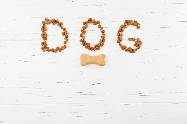 Cane dell'iscrizione su superficie di legno bianca Foto Premium
