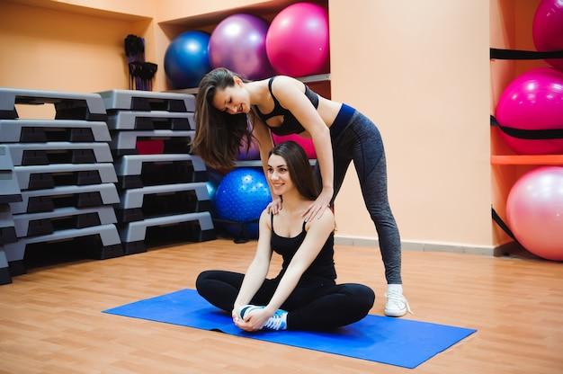Ragazza d'aiuto dell'istruttore che fa allungamento. le donne fanno stretching. Foto Premium