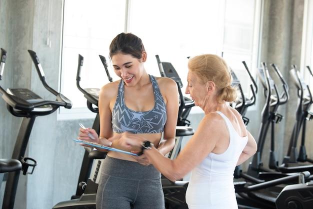 Istruttore con donna senior nel centro di riabilitazione. personal trainer che mostra qualcosa negli appunti del documento. Foto Premium