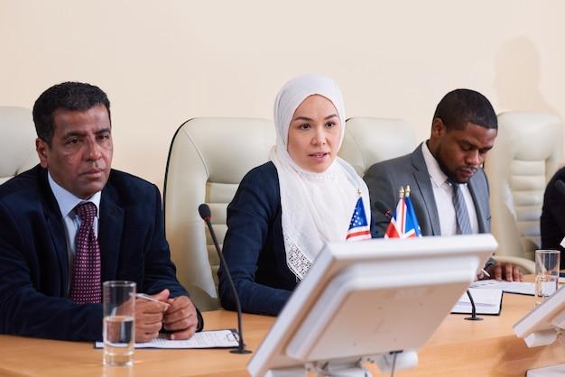Gruppo interculturale di giovani delegati o uomini d'affari che fanno relazioni alla conferenza e discutono i loro punti Foto Premium