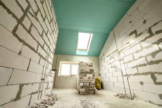 Interno di un appartamento con pareti nude e soffitto in costruzione. Foto Premium