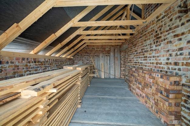 Interno della casa con mattoni a vista non finita con pavimento in cemento, pareti nude pronte per intonacatura e sottotetto con struttura in legno. Foto Premium