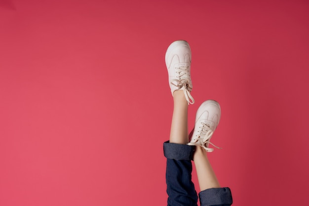 Gambe femminili invertite scarpe da ginnastica bianche movimento street style rosa Foto Premium