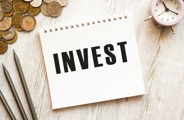 Investire il testo su un foglio di blocco note. le monete sono sparse, matite su una superficie di legno grigia Foto Premium
