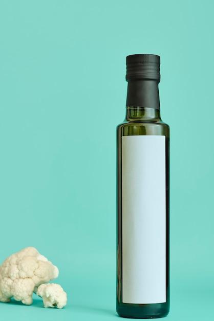 Bottiglia di olio d'oliva isolata su un verde pastello con un bouquet di cavolfiore Foto Premium