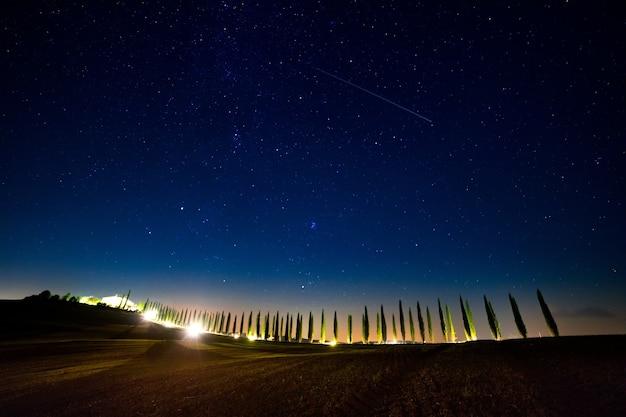 Italia. toscana. cielo stellato senza nuvole sopra un vicolo di cipressi con retroilluminazione Foto Premium