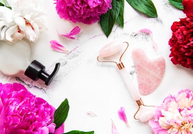 Rullo facciale in giada per terapia di massaggio del viso di bellezza, oli da massaggio e peonie rosa. Foto Premium