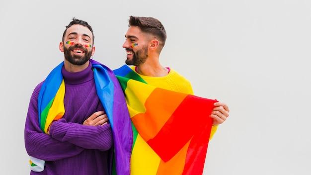 Innamorati gay allegri che tengono la bandiera arcobaleno lgbt Foto Premium