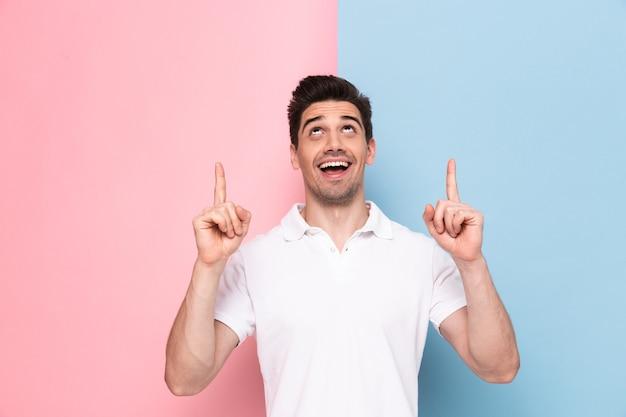 Uomo gioioso con stoppie che punta le dita verso l'alto al copyspace, isolato su un muro colorato Foto Premium