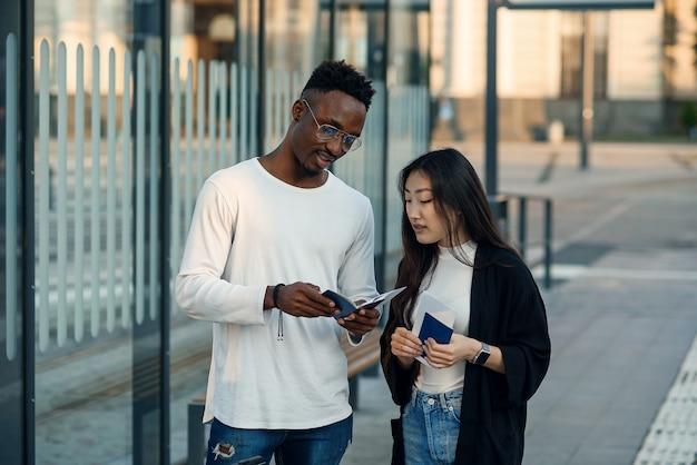 Una gioiosa coppia multirazziale controlla le carte d'imbarco e l'orario di partenza a una fermata dell'autobus vicino all'aeroporto. Foto Premium