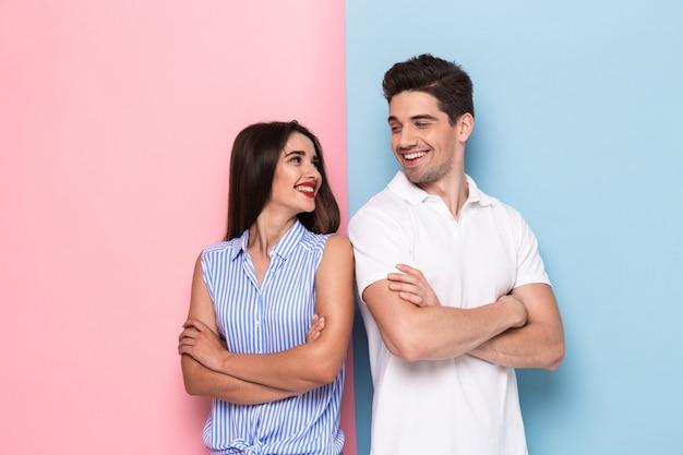 Gioioso uomo e donna in abbigliamento casual in piedi con le braccia incrociate, isolato su un muro colorato Foto Premium