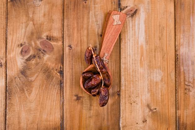 Date succose su un tavolo di legno. frutta secca per una dieta sana. copia spazio Foto Premium