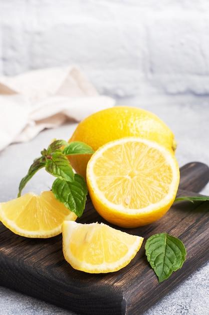 Succosi limoni gialli interi e tagliati con foglioline di menta fresca Foto Premium