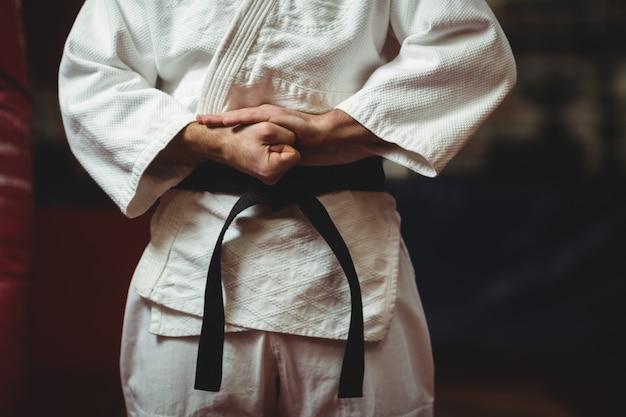 Giocatore di karatè che lega la sua cintura Foto Premium