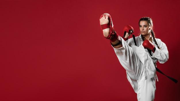 Donna di karatè nell'azione isolata nella priorità bassa rossa Foto Premium