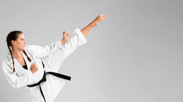 Donna di karatè nell'azione isolata nella priorità bassa bianca Foto Premium