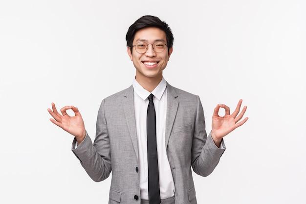 Mantieni la calma e rimanere in salute. imprenditore maschio asiatico sorridente allegro bello, impiegato di concetto che sta calmo, tenendosi per mano nel gesto di zen, rilassandosi, meditando, su una parete bianca Foto Premium