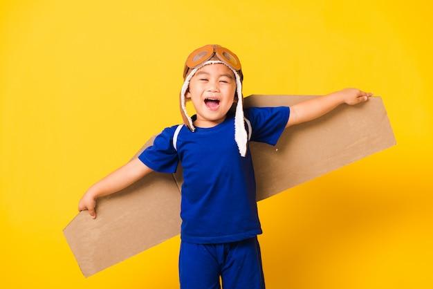 Bambino sorriso ragazzino indossare cappello pilota gioco e occhiali con le ali dell'aeroplano di cartone giocattolo Foto Premium