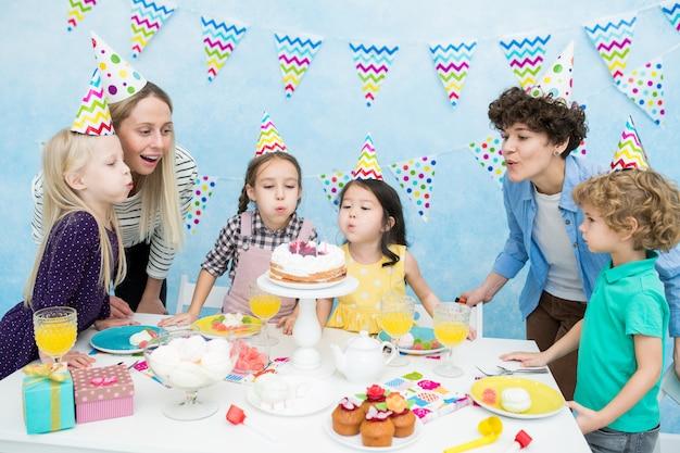 Bambini che spengono le candeline alla festa di compleanno Foto Premium