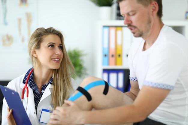 Il paziente di kinesio ha un dottore in ginocchio accanto a lui. concetto di servizi medici Foto Premium