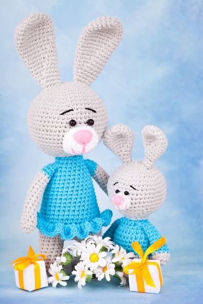 Conigli lavorati a maglia - mamma e figlio con regali e fiori. Foto Premium