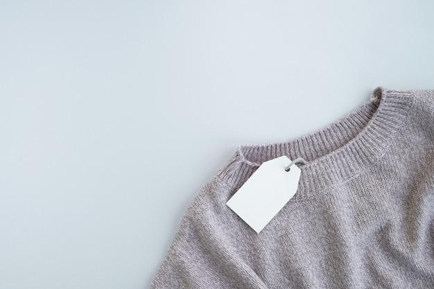 Maglione lavorato a maglia con etichetta vuota sulla superficie grigia. saldi autunnali o invernali Foto Premium
