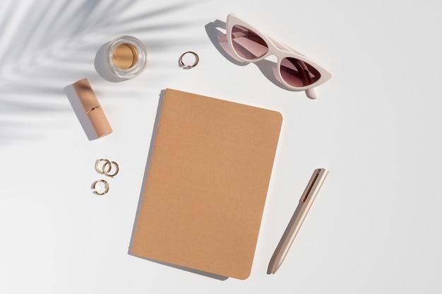 Mockup di quaderno con copertina in carta kraft. scrivania trendy da donna. accessori di bellezza, gioielli e ombra di foglie di palma. lay piatto con copia spazio. Foto Premium