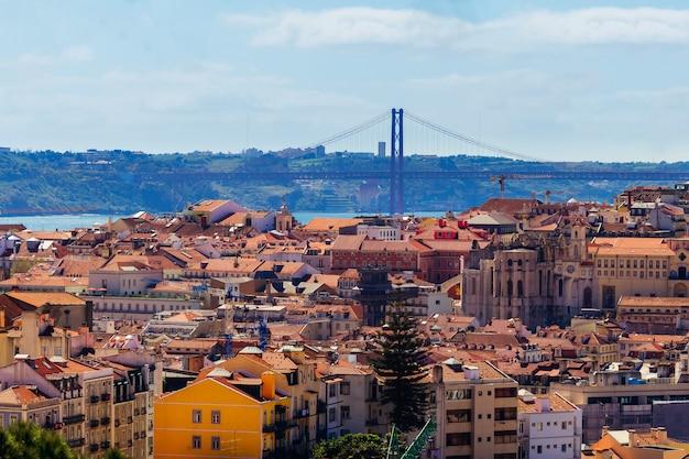 Paesaggio dei tetti rossi e del ponte distante sopra il fiume a lisbona durante il giorno soleggiato Foto Premium