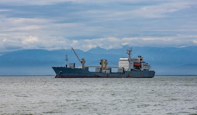 Grande nave porta-container che naviga contro il vulcano Foto Premium