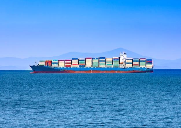 Grande nave portacontainer in mare blu Foto Premium