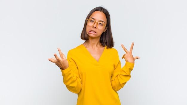 Donna latina che scrolla le spalle con un'espressione stupida, pazza, confusa, perplessa, che si sente infastidita e incapace Foto Premium