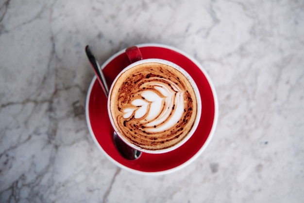 Quest'ultima arte, fiore di rosetta su un cappuccino schiumoso, su una tazza rossa in un caffè. Foto Premium