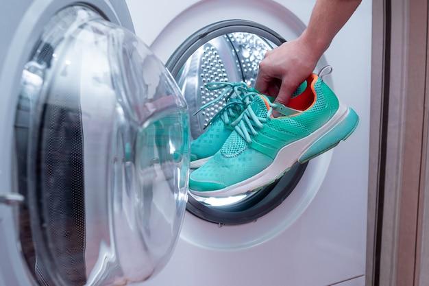 Calzature sporche della lavanderia in una lavatrice a casa. cura delle scarpe Foto Premium