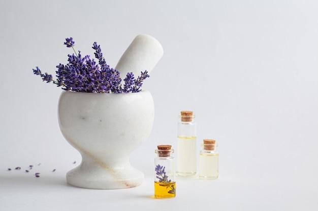 Olio essenziale di lavanda in piccole bottiglie di vetro e fiori di lavanda in un mortaio, sfondo bianco. Foto Premium