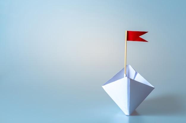 Concetto di direzione utilizzando la nave di carta con bandiera rossa su sfondo blu Foto Premium