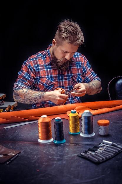 Leather professional crea prodotti di qualità in pelle./leather master al lavoro sul suo nuovo prodotto in pelle nel suo negozio. Foto Premium