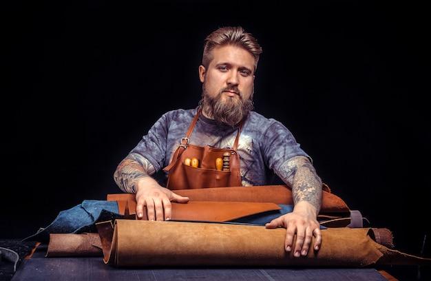 Pelle professionista che lavora la pelle utilizzando strumenti di lavorazione. Foto Premium