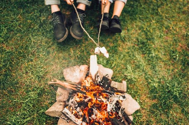 Gambe delle coppie vicino al fuoco. concepl picnic Foto Premium