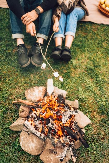 Gambe di coppia vicino al fuoco che arrostiscono marshmallow. concetto di picnic Foto Premium
