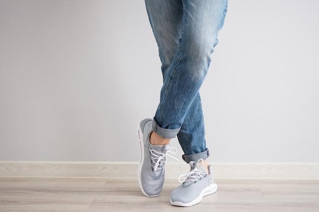 Gambe di un giovane uomo in jeans e scarpe da ginnastica su un muro grigio. Foto Premium