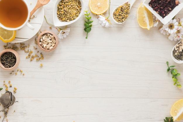 Te al limone; fiori di crisantemo cinese essiccati; erbe sulla scrivania in legno Foto Premium