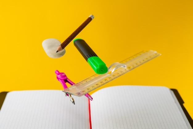 Levitazione materiale scolastico per la matematica su sfondo giallo. istruzione e creatività Foto Premium