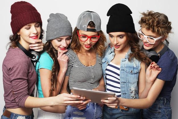 Concetto di stile di vita e persone: cinque amici di ragazze hipster che prendono selfie con tavoletta digitale, studio girato su sfondo grigio Foto Premium