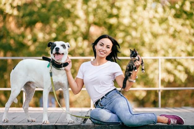 Ritratto di stile di vita di bella donna castana con la seduta del piccolo gatto e del grande cane all'aperto nel parco. Foto Premium