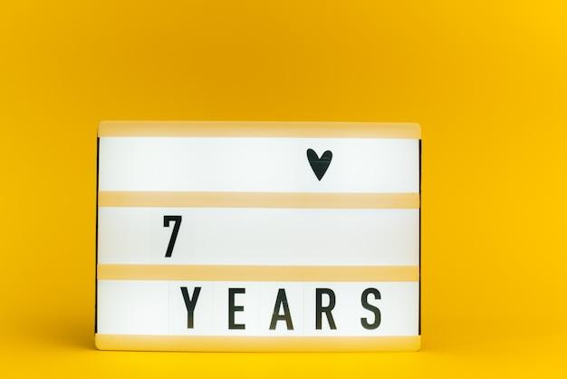 Scatola luminosa con testo, 7 anni, su muro giallo Foto Premium