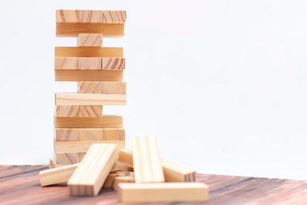 Torre in legno chiaro fatta di blocchi. gioco da tavolo sul tavolo. attività per strategia e concentrazione Foto Premium