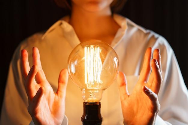 Lampadina tra due mani come simbolo di idee. Foto Premium