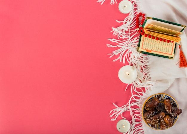 Candela accesa con date succose; santo kuran e perline su scialle bianco su sfondo rosso Foto Premium