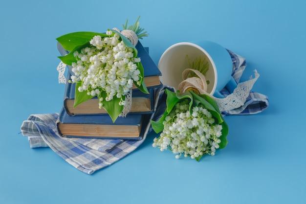 Mughetti e libri su sfondo blu Foto Premium