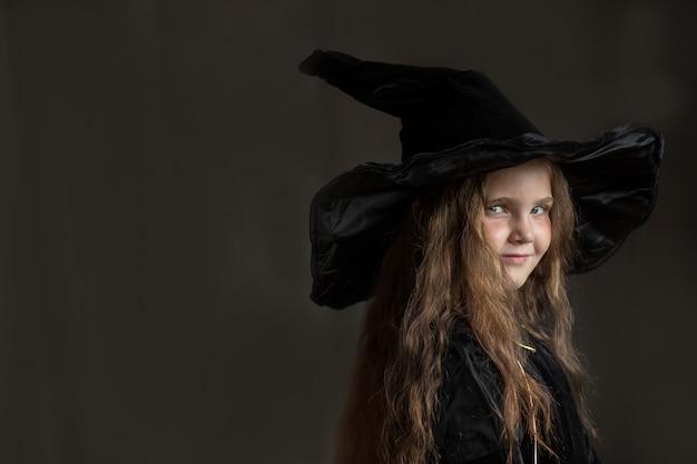 Piccola ragazza in costume da strega di halloween su sfondo grigio Foto Premium